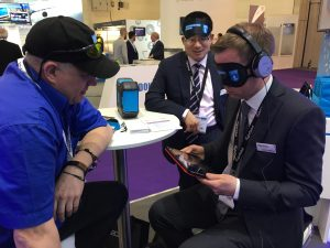 Photo shows a visitor to Bluebox exhibition stand wearing a Guide Dogs UK blindfold and trying Bluebox aIFE